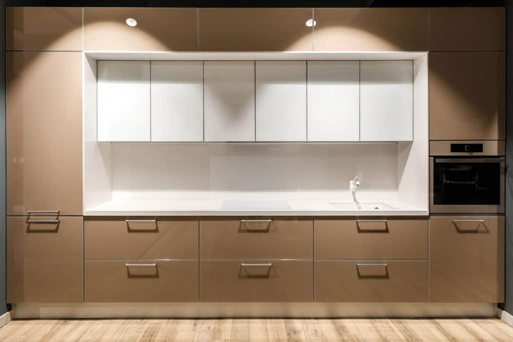 Modern empty area with white paneled main kitchen workstation and wooden paneled lower and upper cabinets