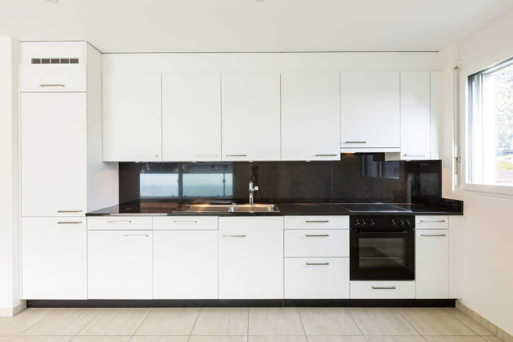 Modern kitchen with white wooden paneled cabinets and a countertop made from dark marble