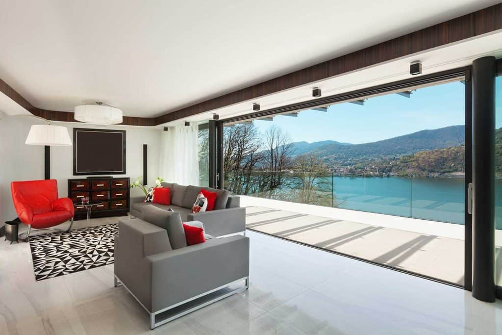 Modern living room with gray sofa and large sliding glass door with view of the river