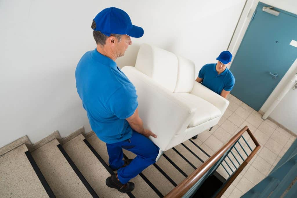 Moving personnel lifting a white couch down the stairs