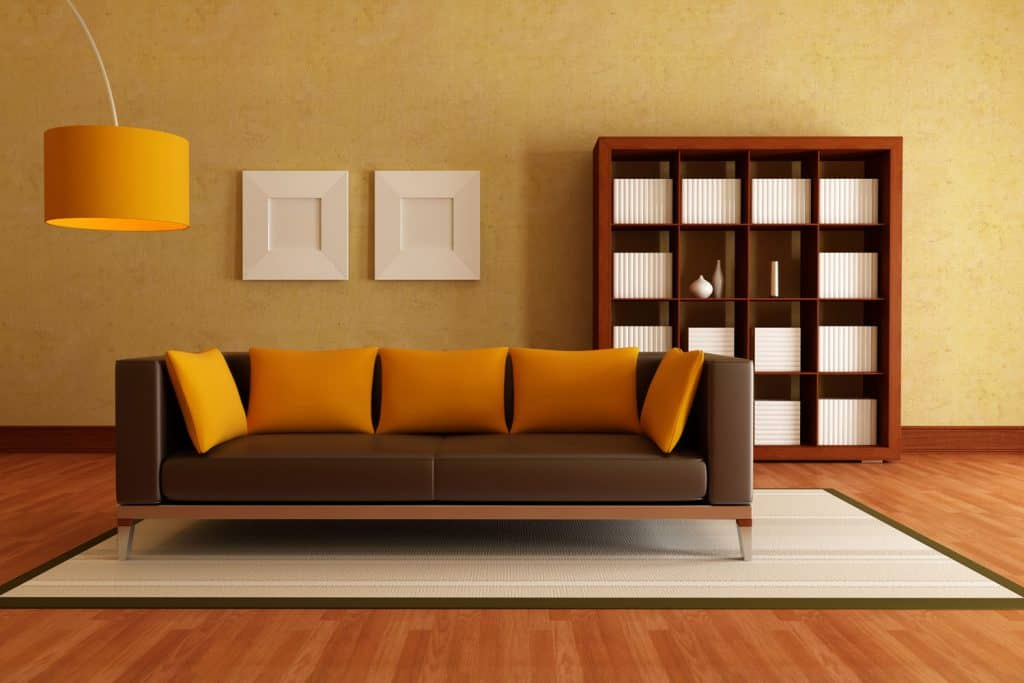 Mustard yellow painted wall with a brown couch and orange throw pillows