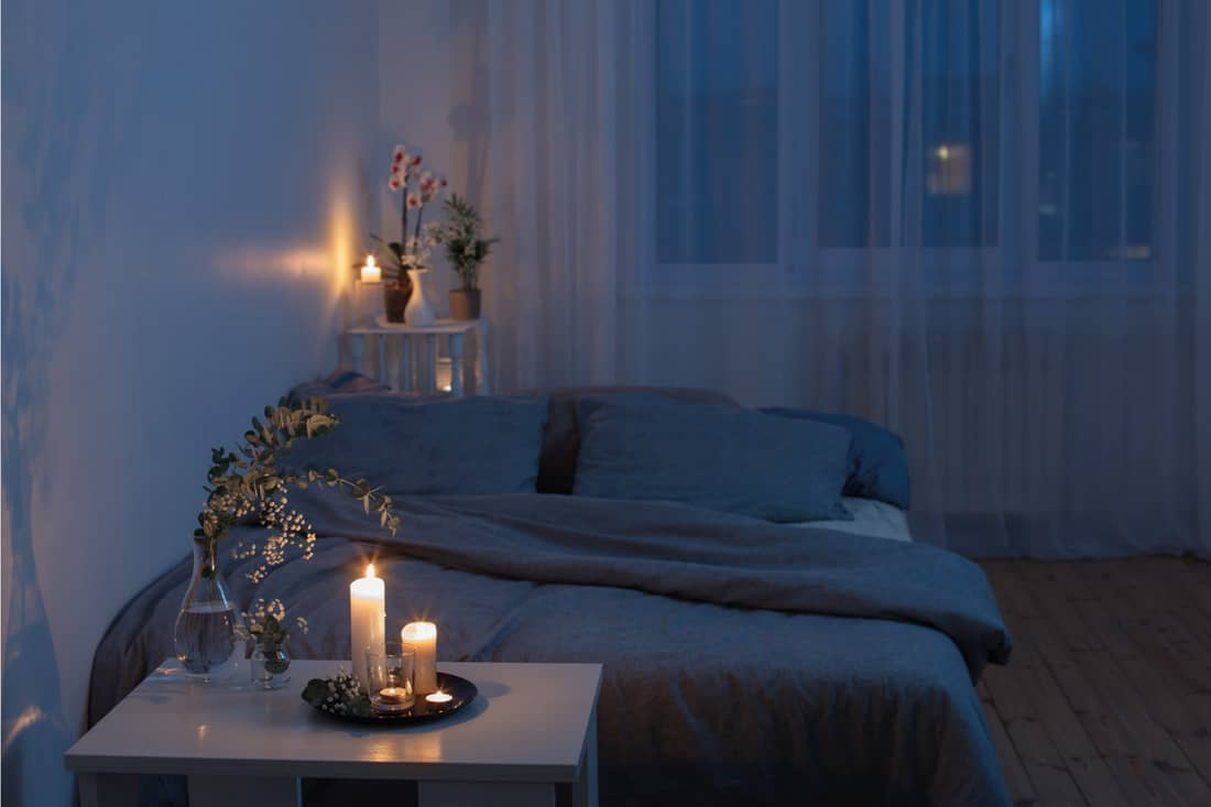 Night interior of bedroom with flowers and burning candles