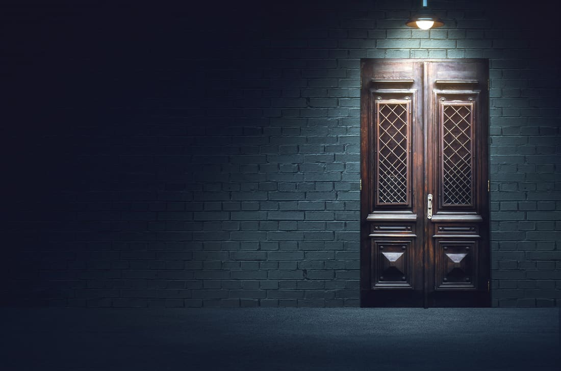 Old fashioned wooden door in front of white brick wall below the spot light of hanging metal lamp.