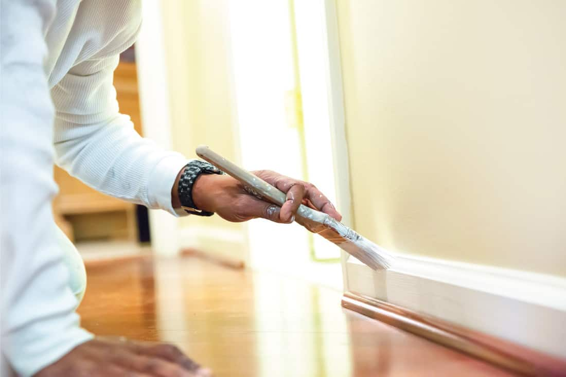Painter using a paint brush to paint baseboard in a home