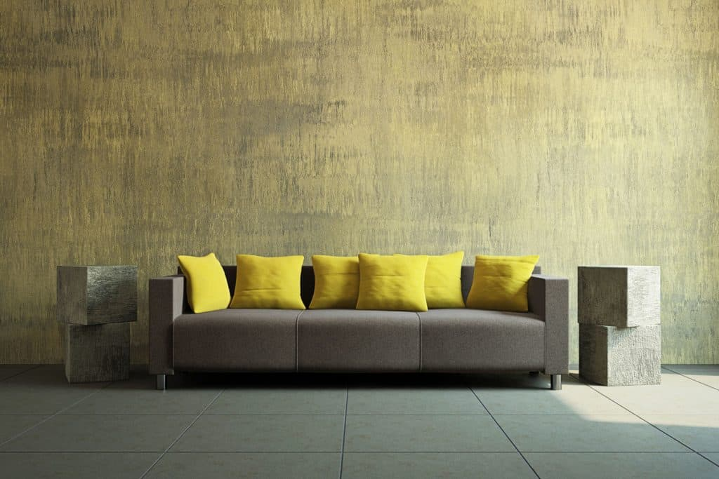 Patterned yellow mustard painted wall with a long sleeper couch with yellow throw pillows