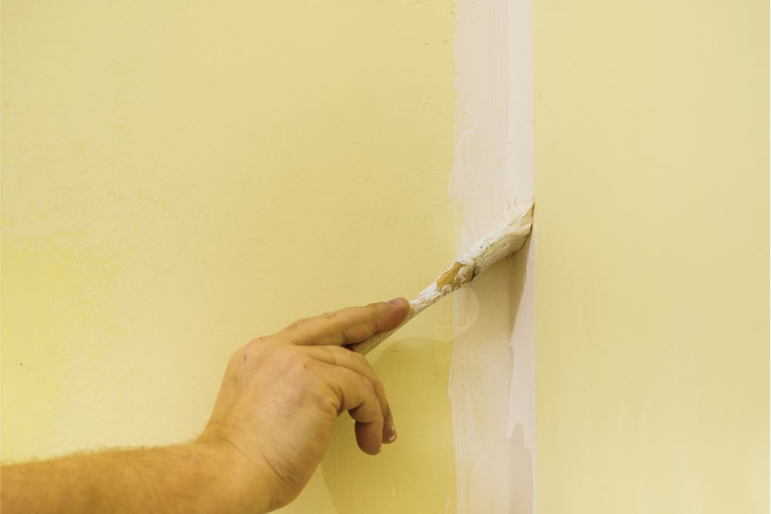 Person appplying white paint on yellow wall edge using brush