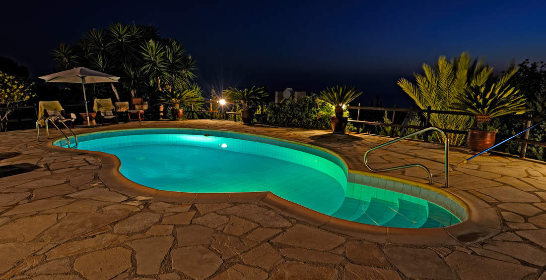 Private swimming pool at night with Deck Rail Lights