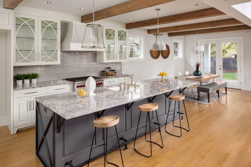 Rustic farmhouse inspired kitchen with white marble countertop and industrial bar stools