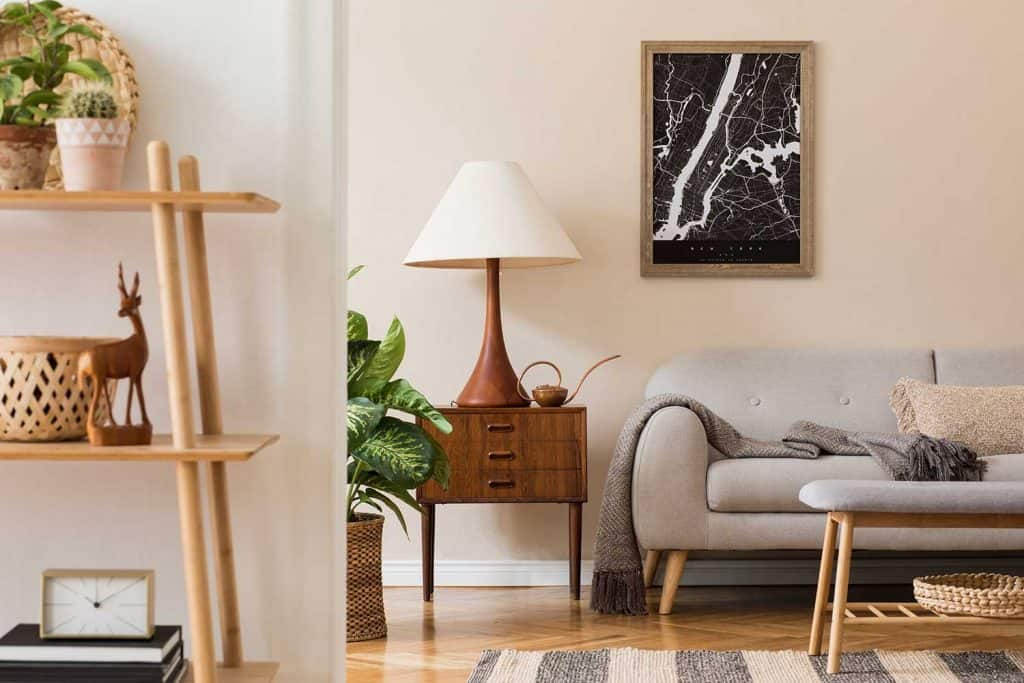 Scandinavian home interior of living room with brown mock up poster frame, design retro commode, sofa, bookstand, rattan basket with plant and elegant accessories