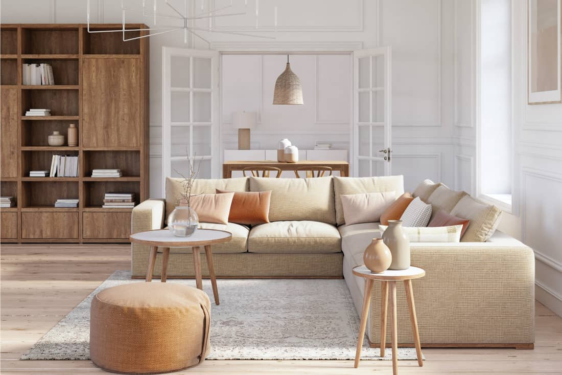 Scandinavian interior design living room with beige colored sectional sofa and wooden elements