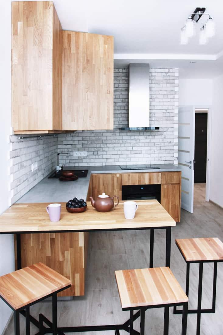 Scandinavian kitchen design, oak furniture against a gray flooring and wall