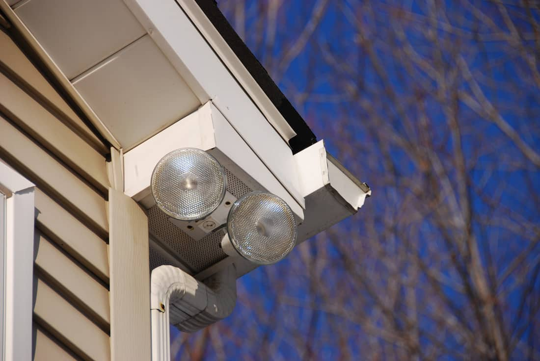 Series of 2 floodlights attached to house corner to provide security and lighting to the driveway below.