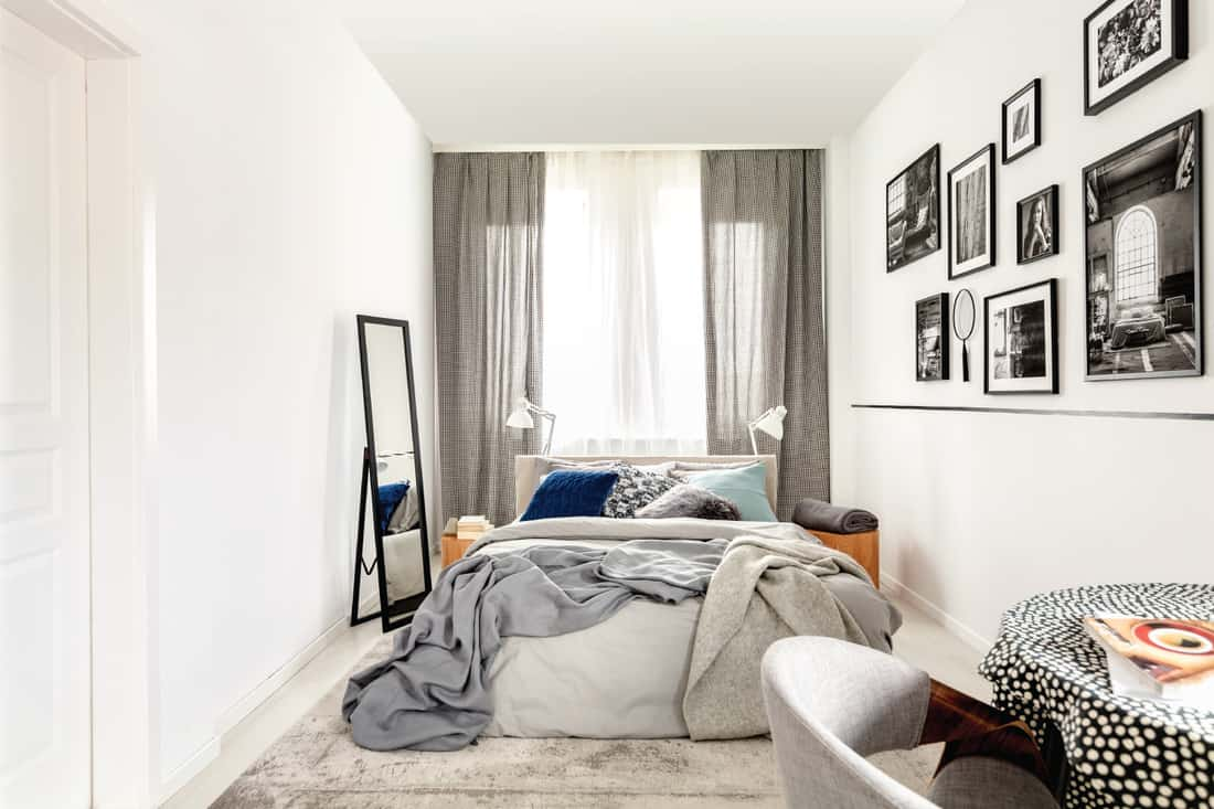 Small bedroom interior with king-sized bed, mirror, black and white photos on the wall, and framing curtains on windows