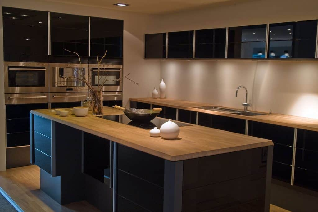 Small contemporary themed dining are with dark paneled kitchen cabinetry with wooden countertops