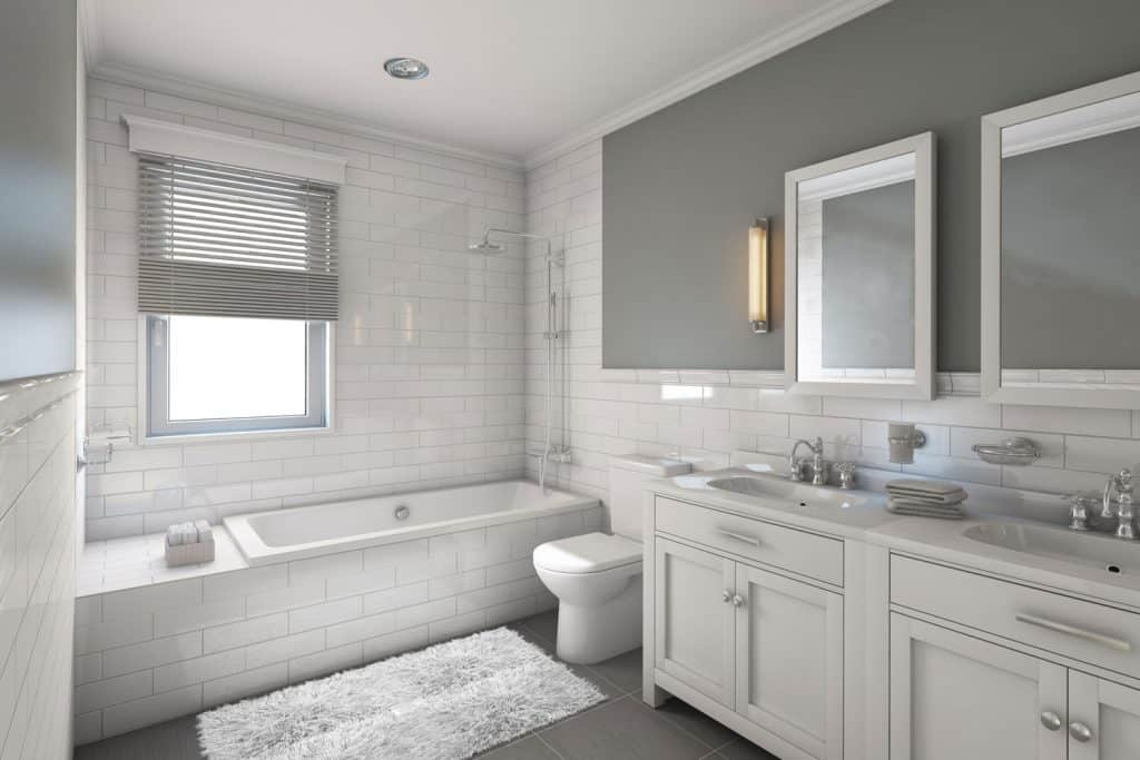 Small gray 3/4 bathroom with a small bathtub, small square mirrors and gray tiles