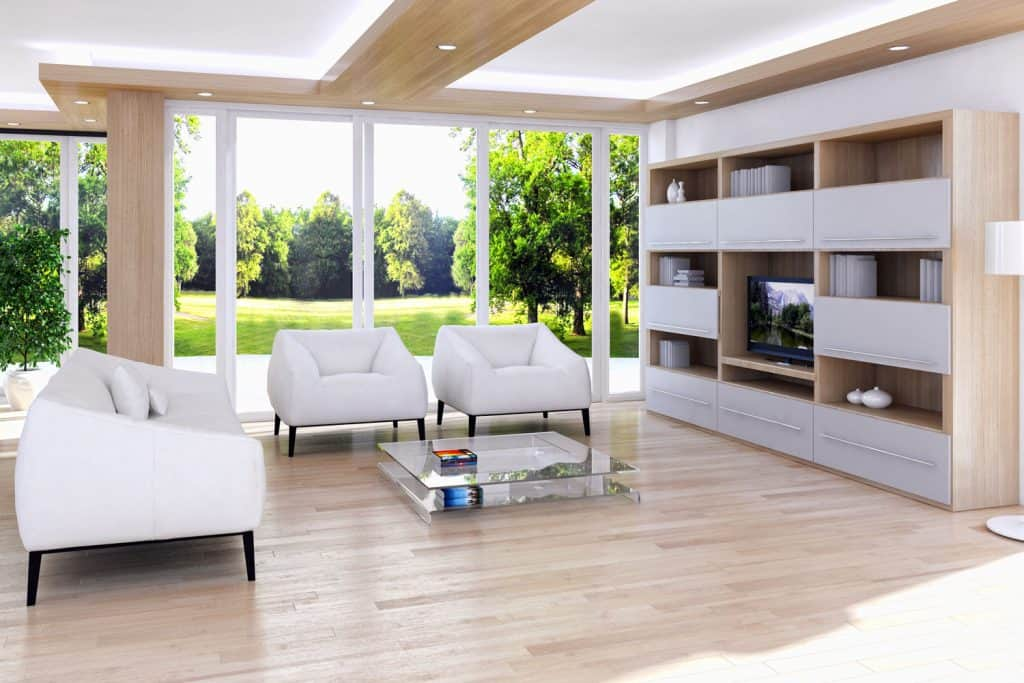 Spacious contemporary living room with white sofas, glass coffee table, laminated vinyl flooring, and a white paneled cabinet section