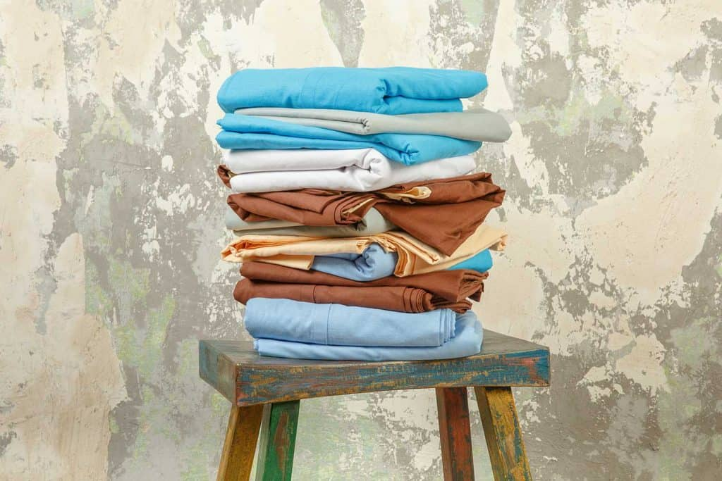 Stacks of colorful bed linen textiles clothing on stool