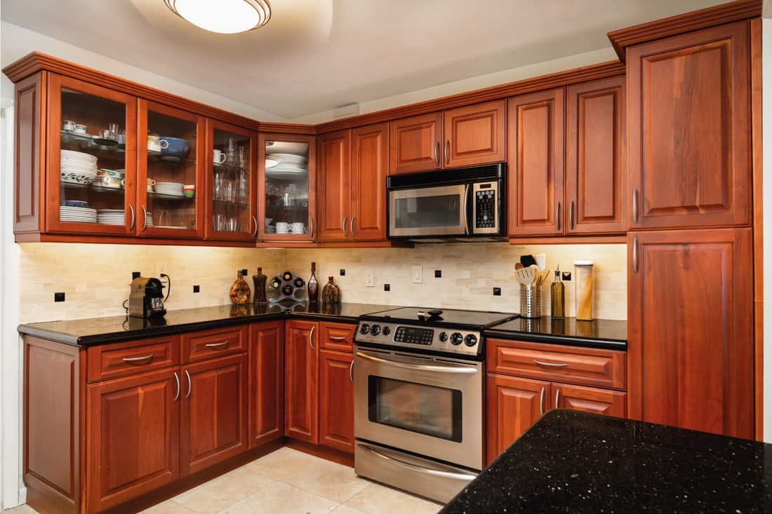 Traditional cheery wood cabinet home kitchen with a black granite countertop, beige walls and floors
