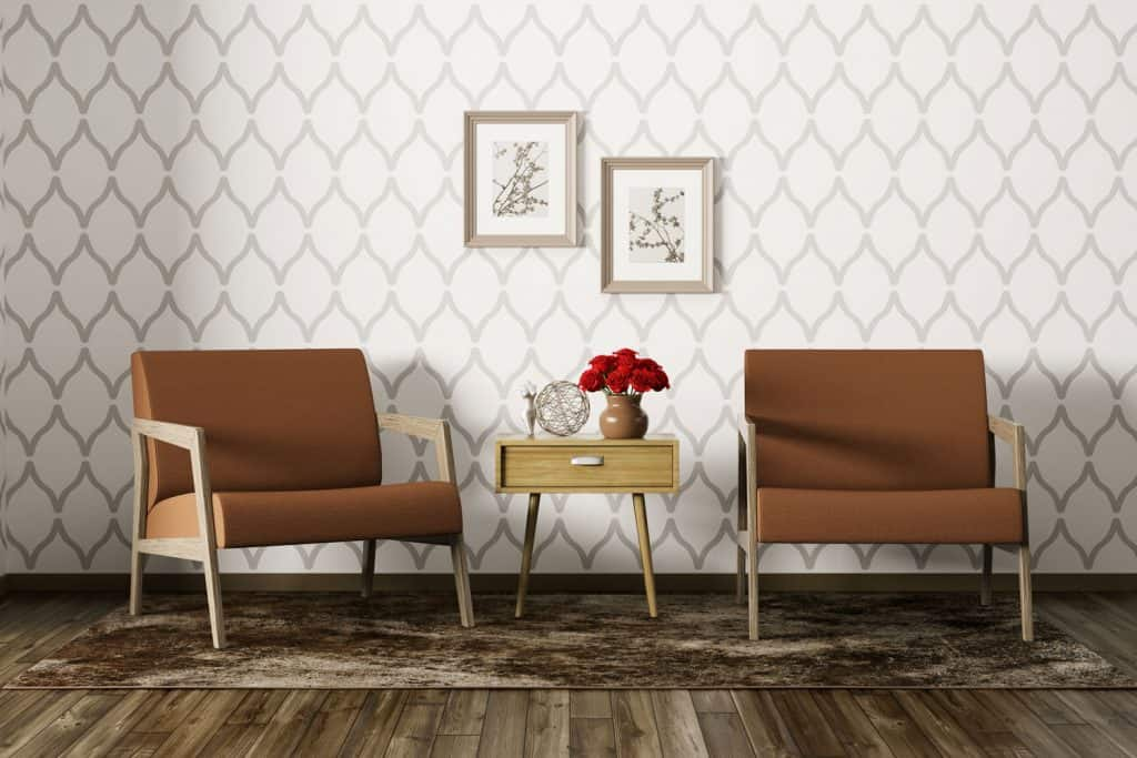 Two brown sofas with an end table in the middle on a brown and gray rug