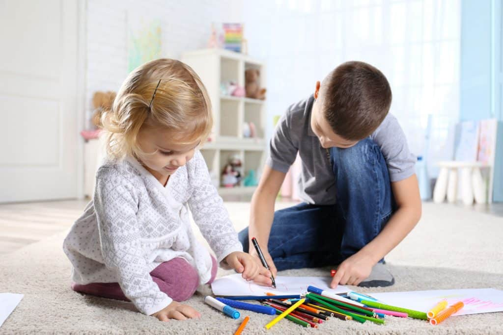 Two small children using markers to draw while sitting on the carpet