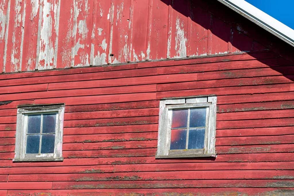 Weathered wood siding on an antique building with windows