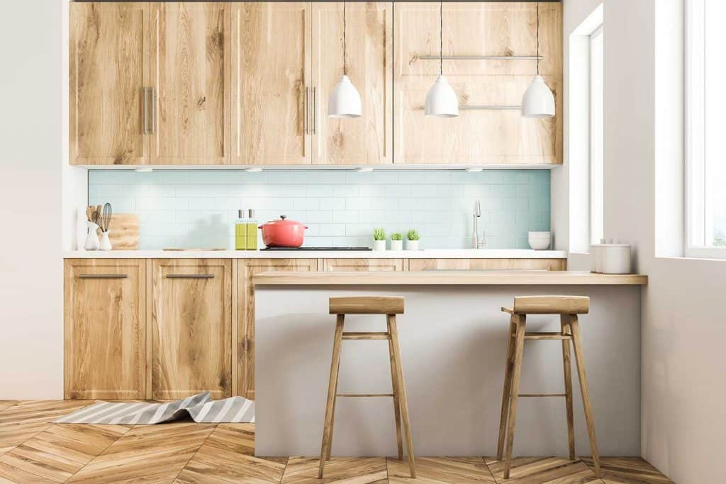 White Scandinavian style kitchen interior with blue tiled and white walls, a wooden floor, wooden countertops and cabinets and a bar with stools
