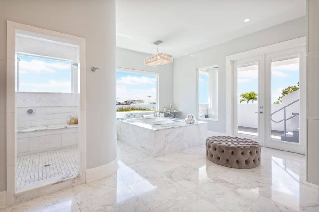 White bathroom with white marbled flooring, huge windows, an ottoman on the middle with a bathtub on the middle