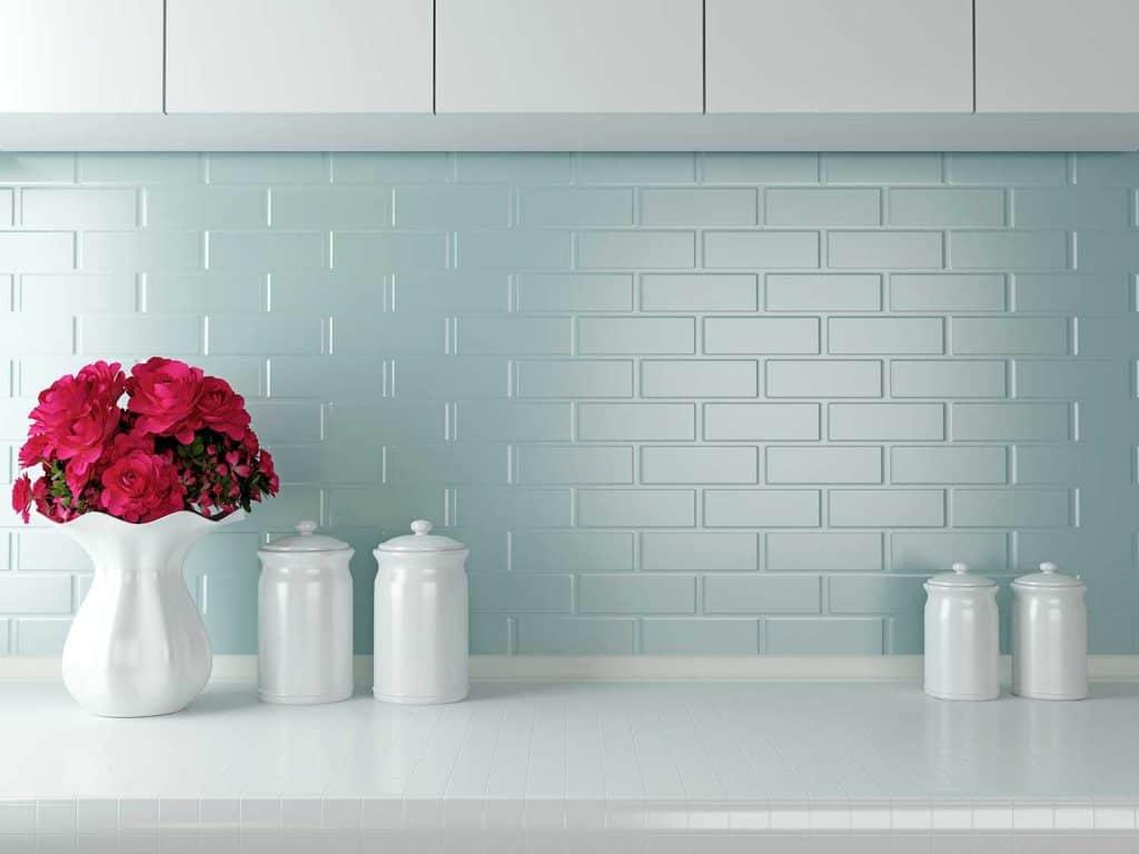 White kitchen design with teal blue brick walls