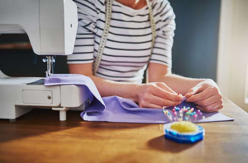 Woman hands sewing on a machine