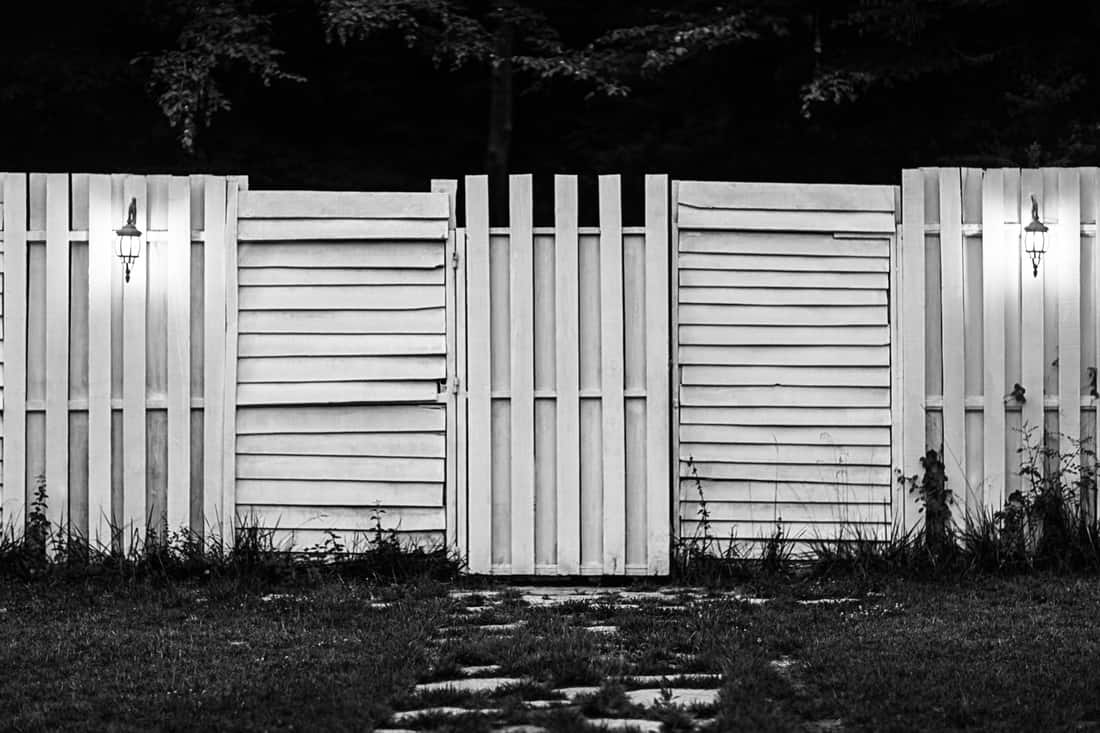 Wooden gate and fence with Baluster Lights on the back of the home garden