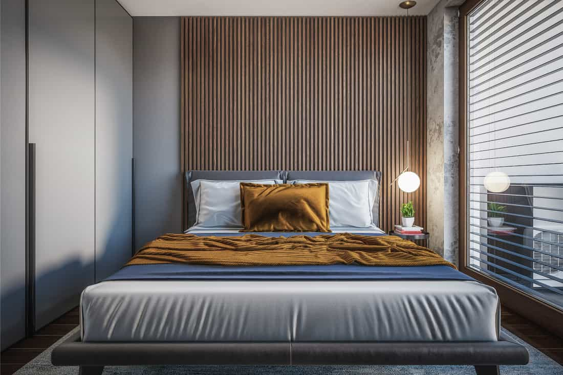 Accent wall above a king-sized bed with pillows and blanket