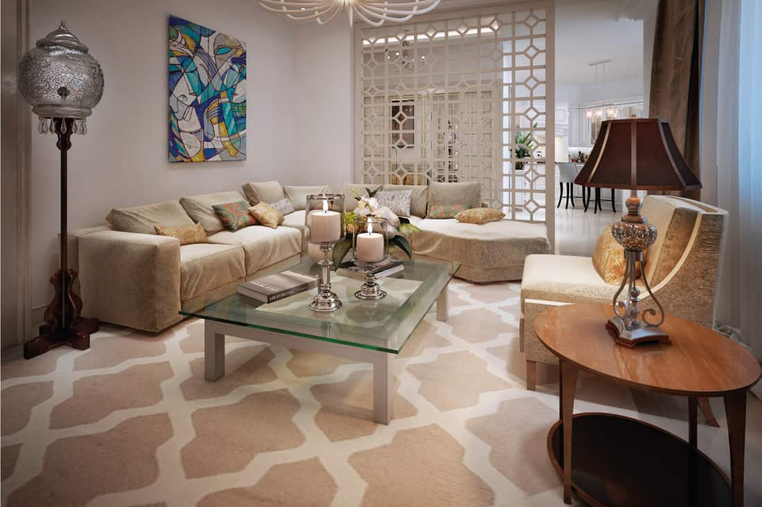 Average size sectional couch in an Arabic style living room with chandeliers and center table