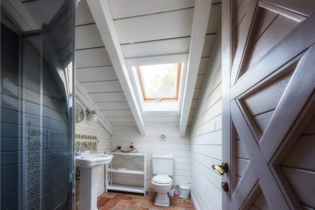 Bathroom in cottage house with mismatched faucet and doorknob
