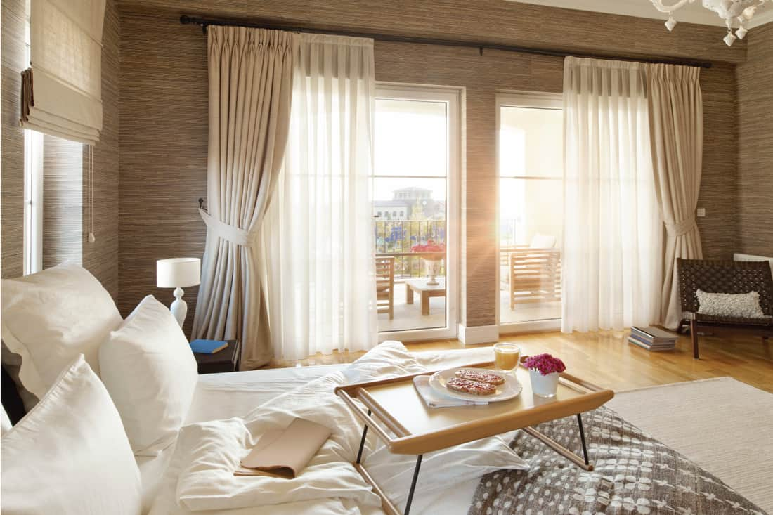 Bedroom with wide windows, long curtains and breakfast in bed, What Are The Standard Curtain Panel Sizes (Height and Width)