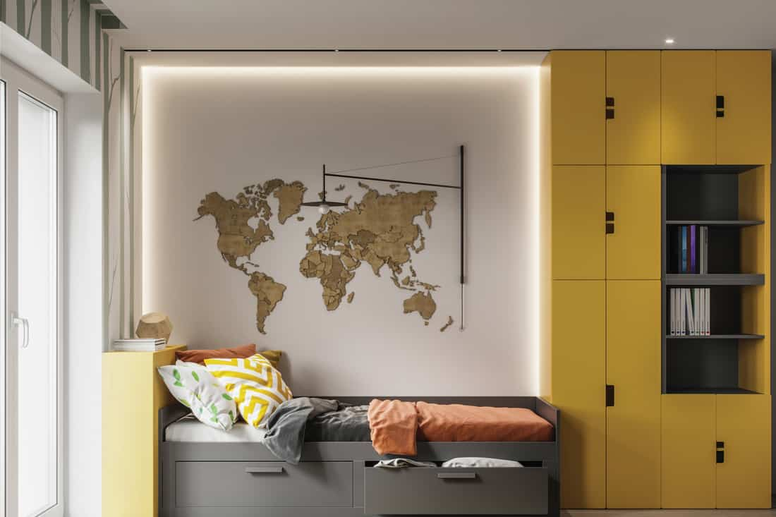 child's room with single bed and a wooden relief world map on the wall