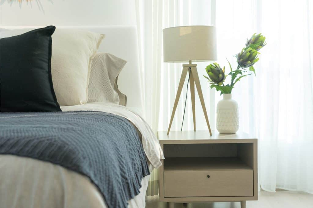 End table beside a bed with dark blue blanket used as a nightstand near a curtained window