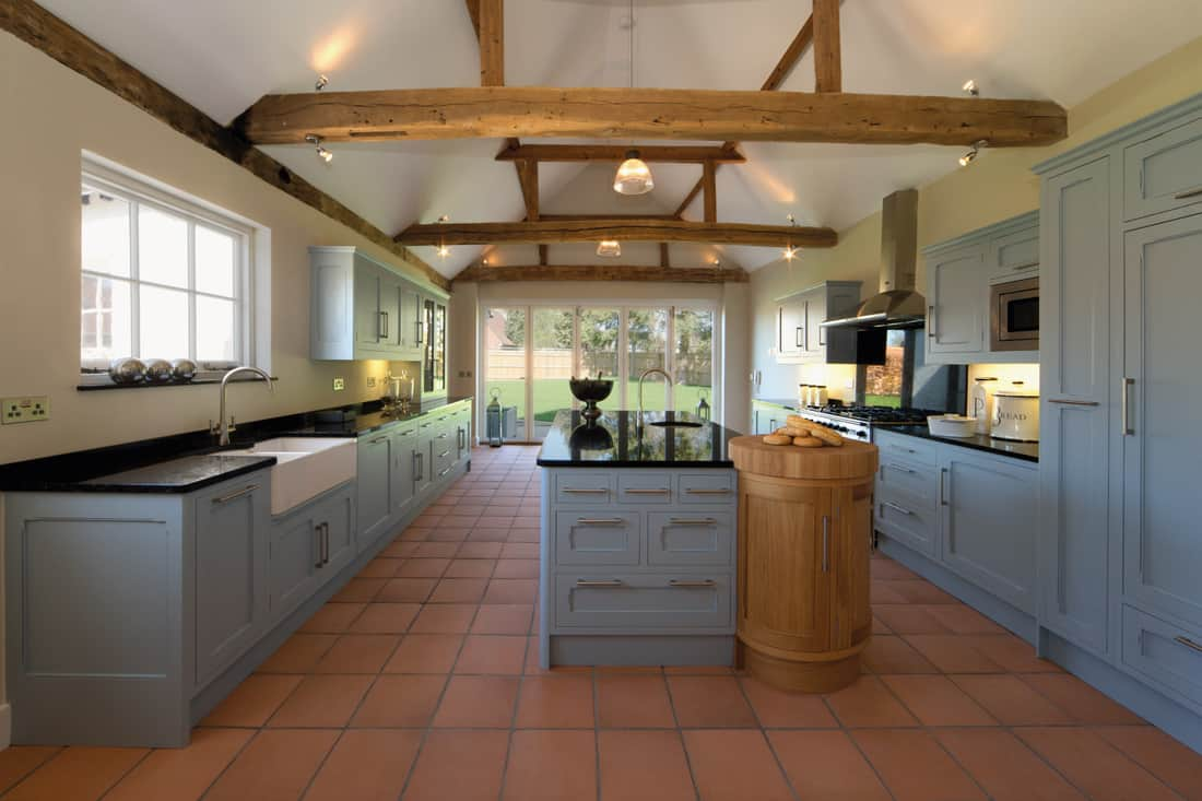Farmhouse kitchen with oak beams at the vaulted ceiling, large kitchen island, teracotta flooring and powder blue cupboards