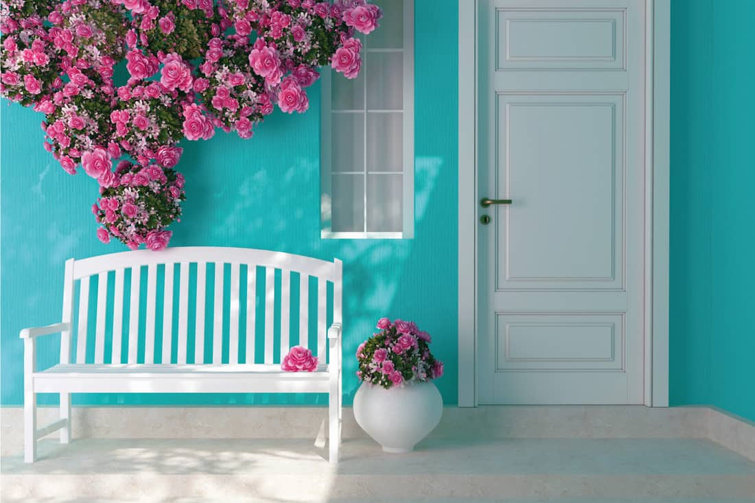 Flowery front porch with white wooden bench