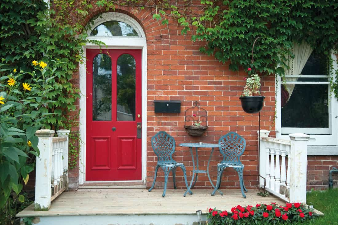 front porch with red door and basket hung on the porch wall