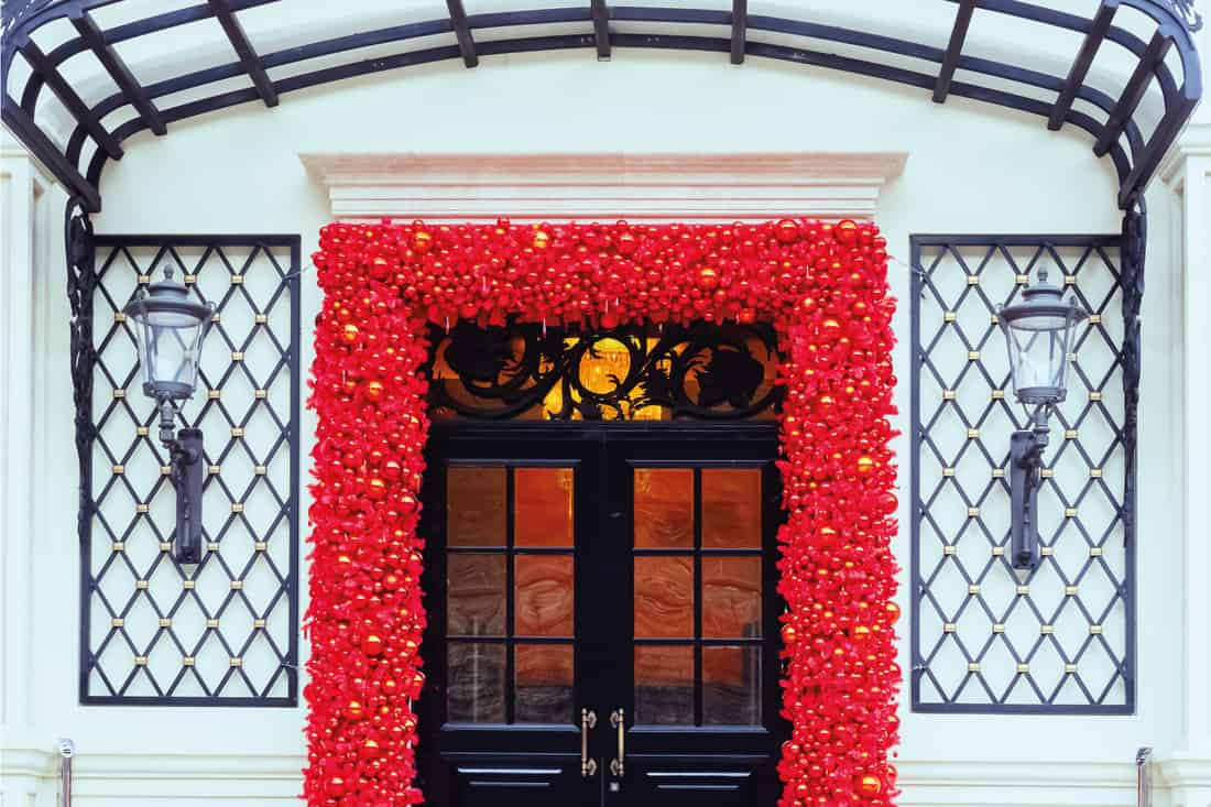 front porch with red new years decor and lamps on wrought iron grilles on the sides