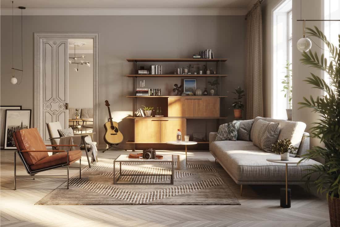 Fully furnished modern living room in gray flooring and walls with accented brown and gray furniture