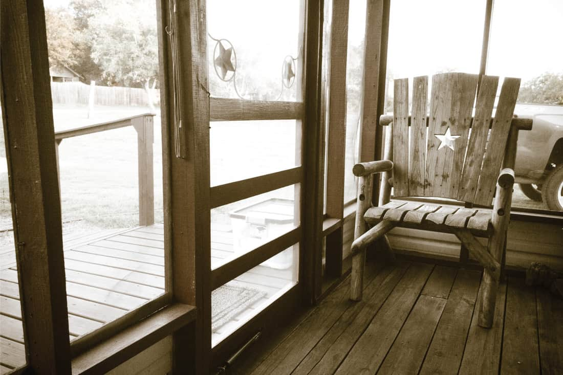 image of an empty chair on a screened-in porch