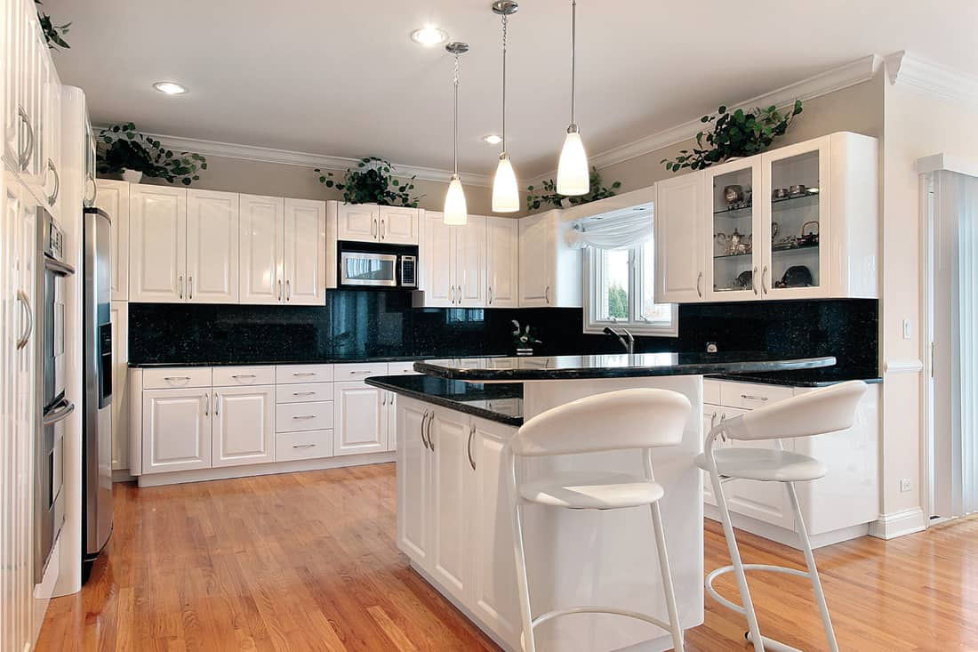 kitchen with black countertops and all white cabinets and fixtures