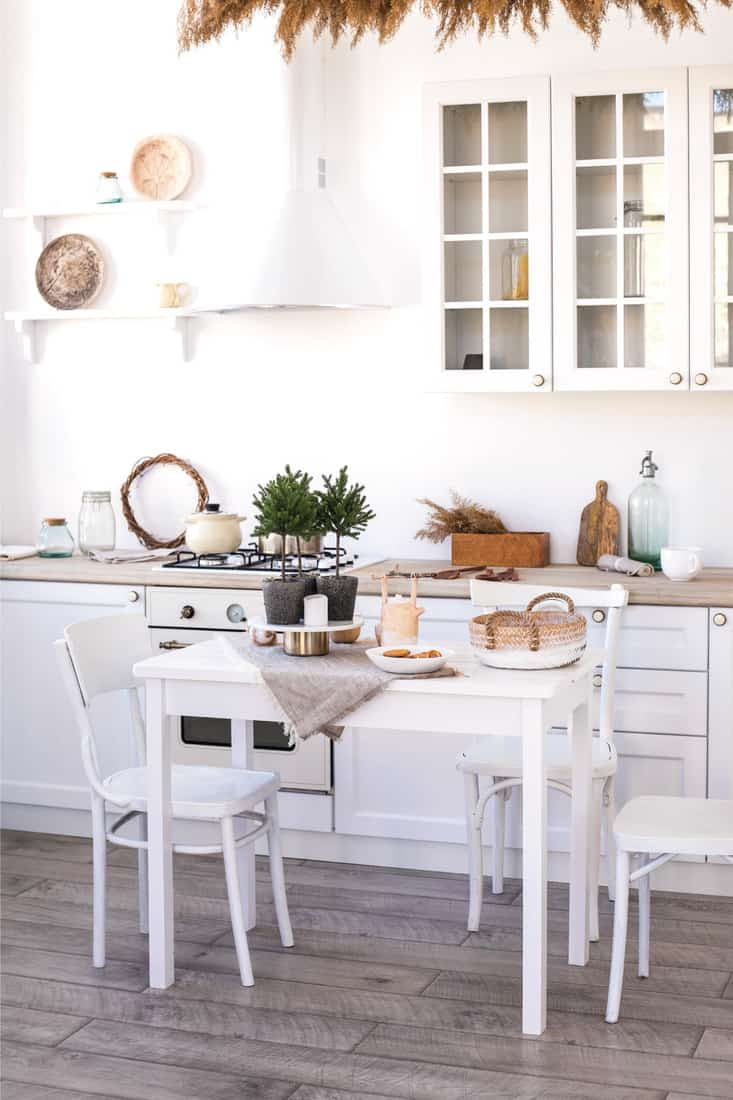Kitchen with gray flooring and white wooden chair, table and cupboards