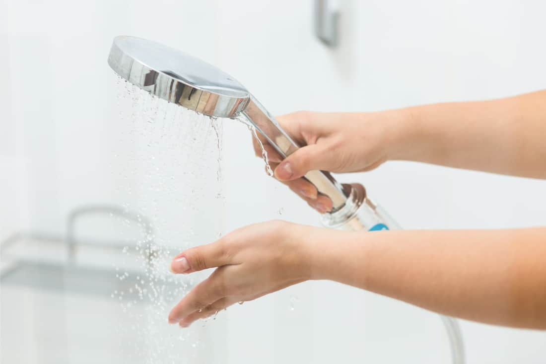 A lady testing water coming out of a shower head