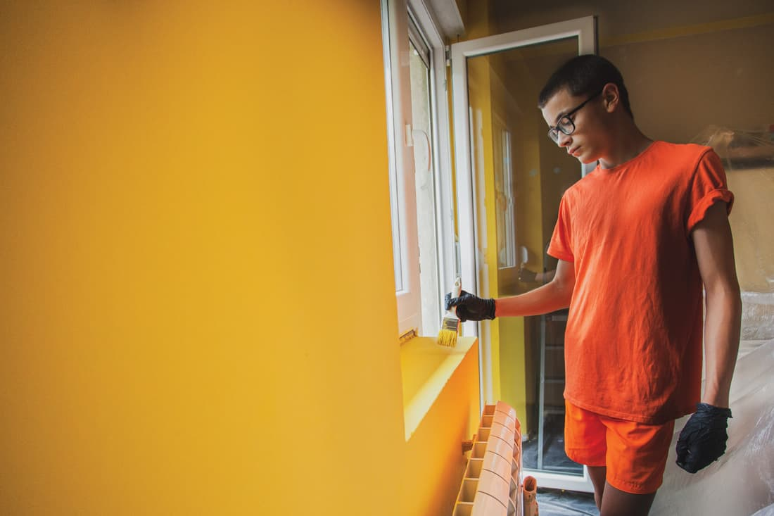 male teenager painting his room using a paint roller with bright yellow