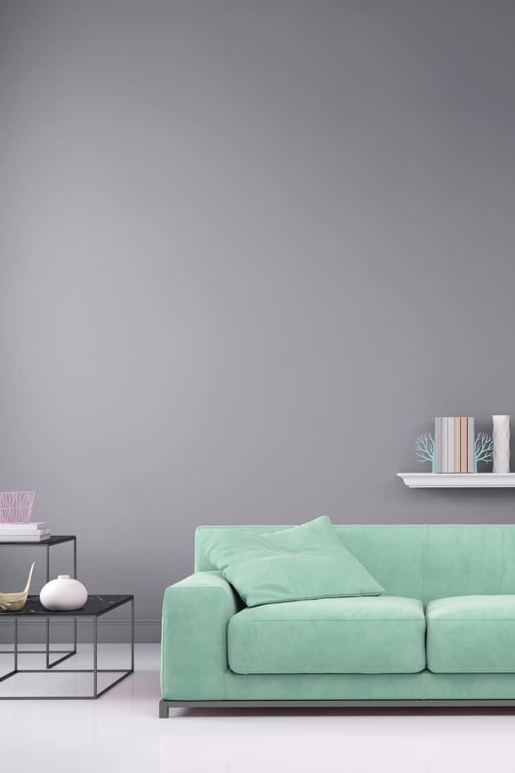 mint green colored pastel sofa with a gray wall background