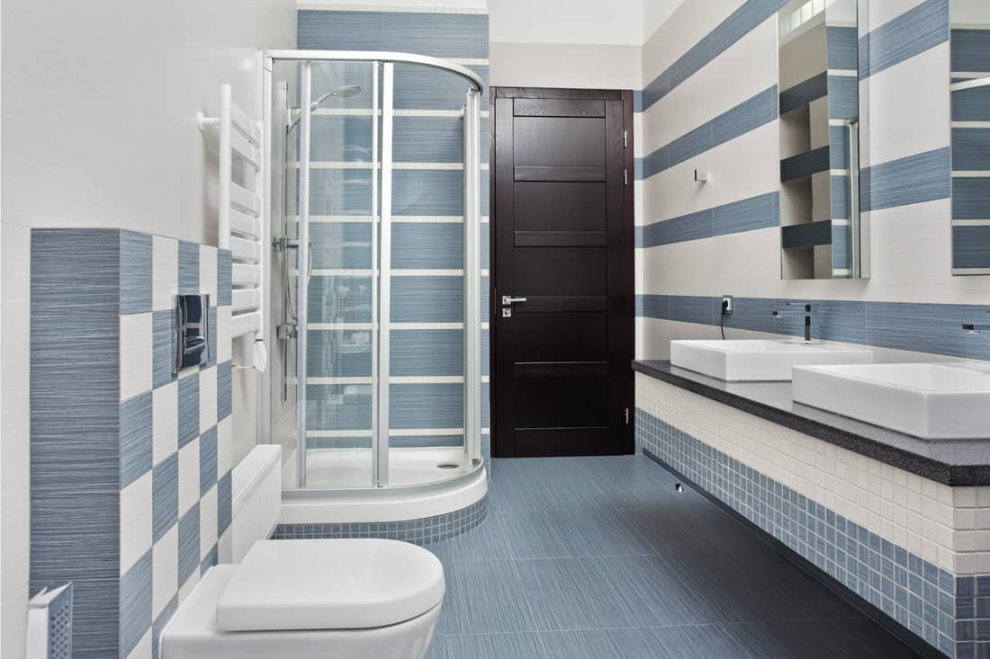 Modern bathroom in blue and gray, matching faucet and doorknob