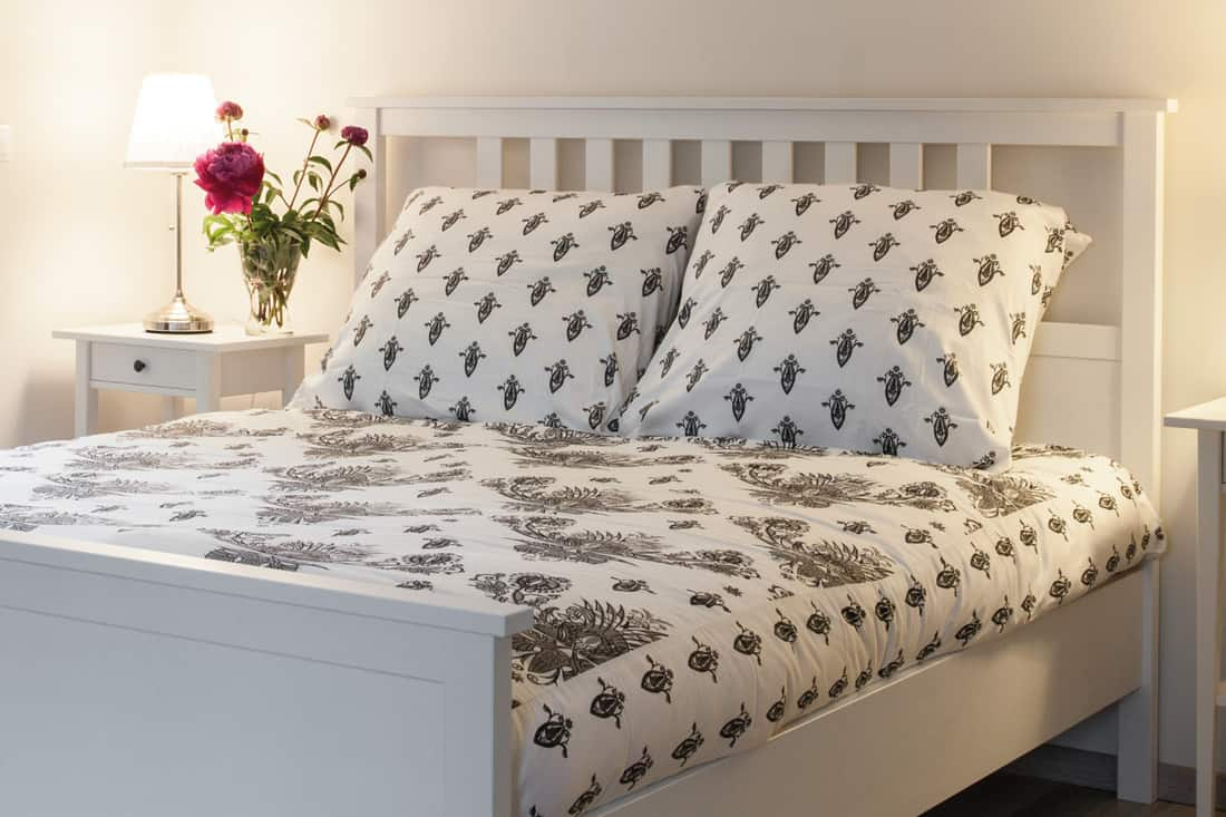 modern full double bed with printed pillowcases and bed sheet, lamps on nightstands