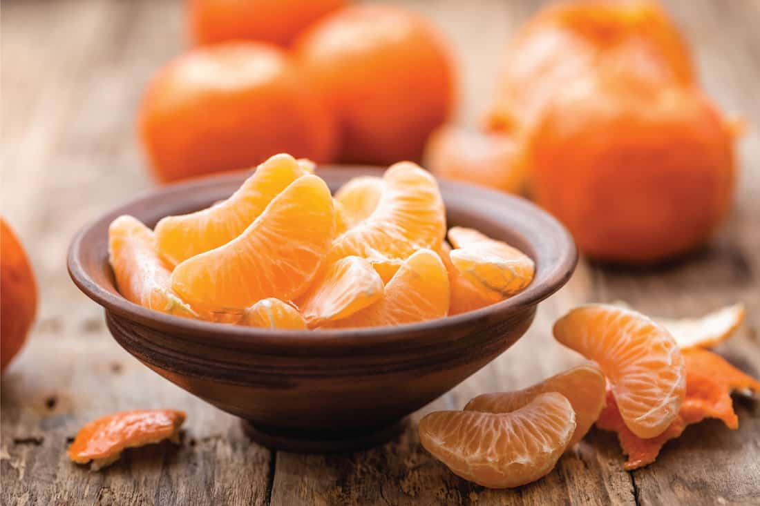 Peeled tangerines in a bowl on a wooden table